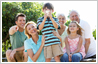 Photo editing example [Edit person in group]: This is a family group photograph spanning three generations. The little boy is holding a cell phone to his face, covering his eyes entirely. The challenge is to move the cell phone down and bring his eyes into view! Open eyes at that!