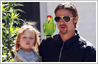 Photo editing example (before & after) of inserting a new element in a photo. A parrot has been added to Brad Pitt's family photo.